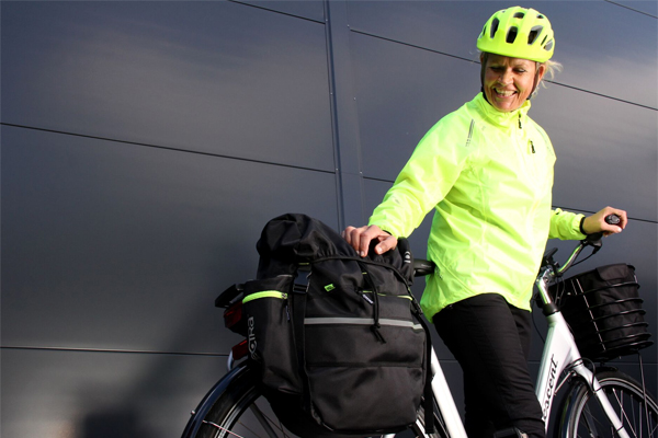 Person kitted in reflecting rain jacket and helmet with carrrier bags on her bike