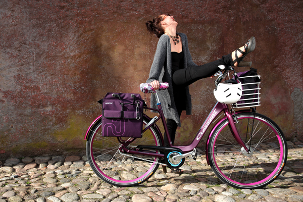 Woman with purple town bike with matching bike accessories