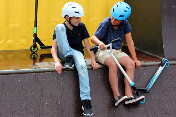 Kids with green and blue scooters and matching helmets